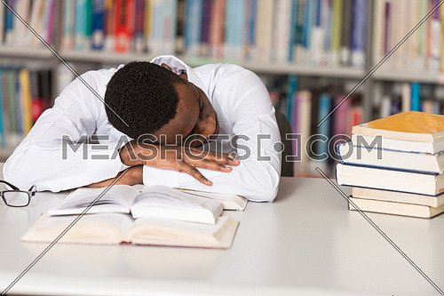 Sleeping African Student Sitting And Leaning On Pile Of Books In College - Shallow Depth Of Field