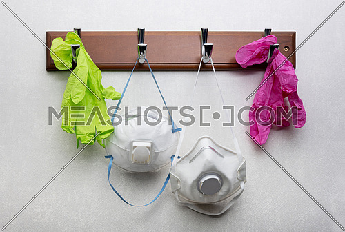 Close up white disposable facepiece respirator masks with exhalation valves and disposal gloves hanging on clothes rack as essential safety accessory during pandemic, low angle view