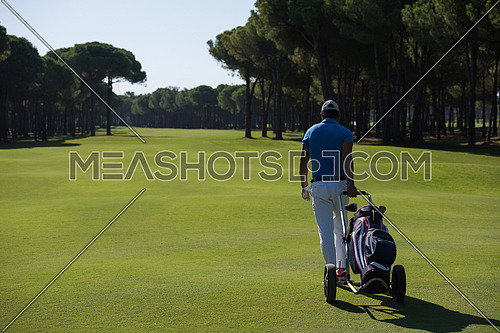 handsome middle eastern golf playerwalking with wheel bag at course on beautiful  sunny day