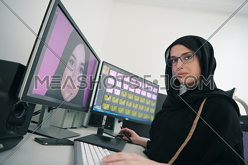 Young muslim girl working on the computer from home. Female photo editor at working place. Freelancer using two monitors while doing job