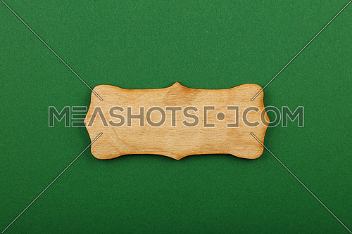 Figured ornately shaped blank wooden sign with copy space in center of green design paper background, title slide template