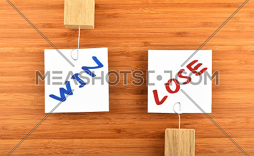 Win lose, two white paper notes with marker hand written words, wooden holders in different directions on bamboo wooden background for presentation