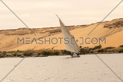 Ferry boat in River Nile, Aswan, Egypt. And sand hill in the background and some bushes