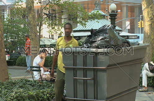 Long shot for African male Park worker disposes of garbage in park at New York City at day