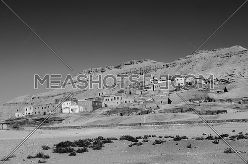 an old city build in between the mountains in black and white in Luxor city monochrome