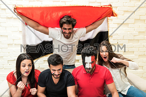 group of young people sitting on a sofa cheering for a football match in front of white table holding egyptian flags and one of them has egyptian flag paint on his face