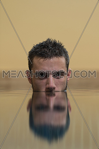 Young Man Swimming In Pool With Face Half Submerged Looking At Camera