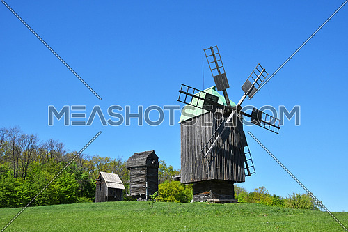 Rural meadow landscape with three old wooden windmills, forest trees and clear blue sky