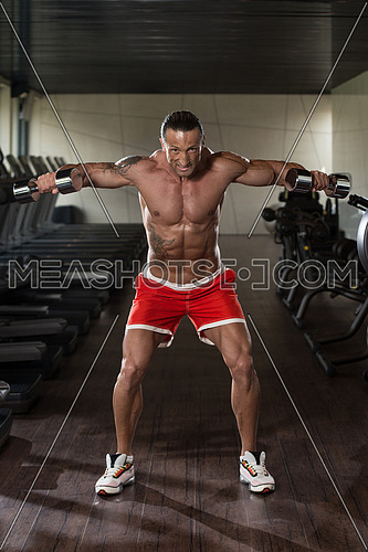 Muscular Mature Man Doing Heavy Weight Exercise For Shoulders With Dumbbells In Modern Fitness Center
