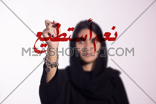 "Arabian middle eastern business woman writing with a marker on virtual screen in arabic ""yes i can"" suggesting women empowerment isolated on white background"