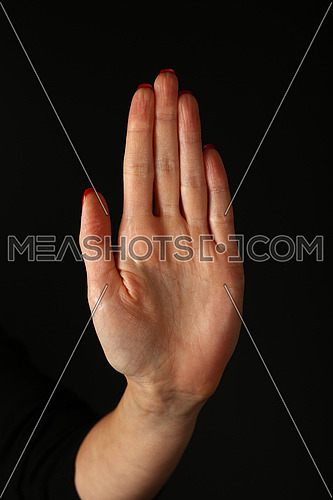 Woman hand palm showing stop gesture over black background, side view