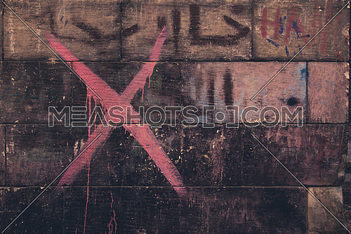 A red X sprayed on a brick wall