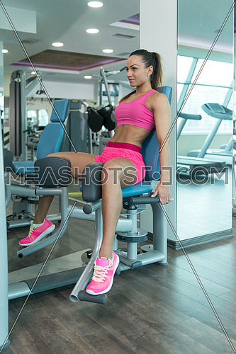 Young Fitness Woman Working Out Legs On Machine In A Fitness Center - Leg Exercise