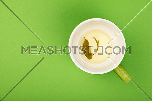 One empty finished clear green oolong tea in big cup with saucer with leaves floating on green paper background, top view, point of view, close up