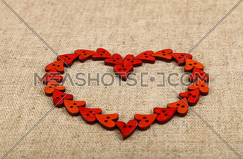 Red heart shaped handmade wooden sewing buttons frame on linen canvas, low angle view, close up