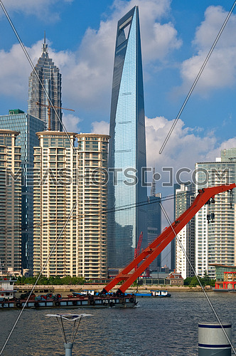 shanghai pudong view from puxi ,with big red crane boat crossing  huangpu river