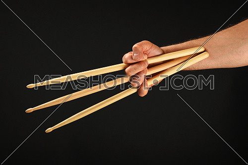 Famous wolverine claws heroic gesture, man hand holding three wooden drumsticks over black background, front view, horizontal