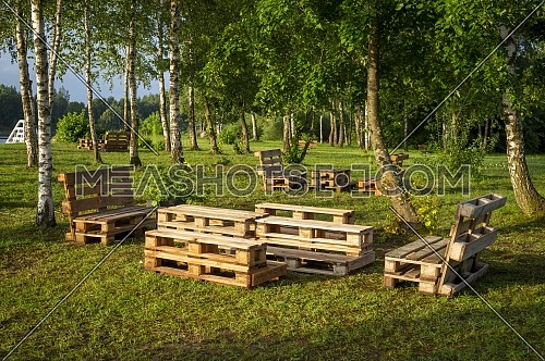 Outdoor furniture made from wood pallets surrounded by trees and greenery in summer sunshine