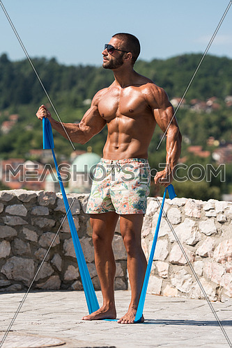 Sportsman Exercising With A Resistance Band Outdoors