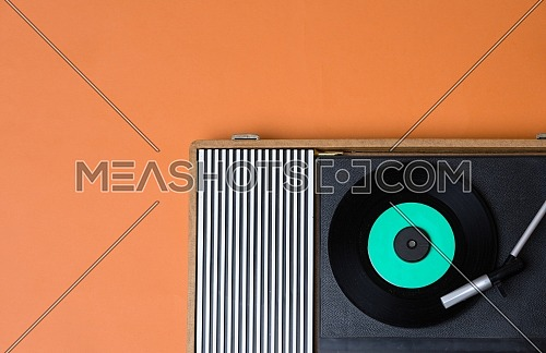 Retro vinyl player and turnable on a yellow background. Entertainment 70s. Listen to music. Top view.