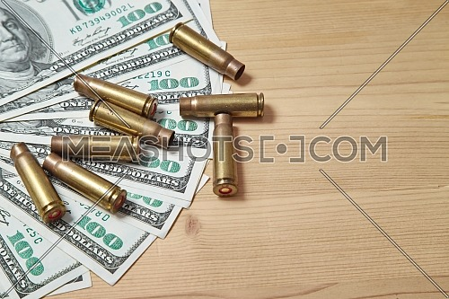 Closeup for used bullet shells and dollars on wooden table.