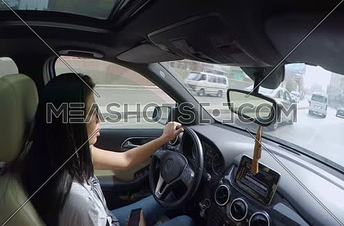 Inside car shot for female drive while using phone