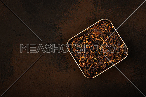 Close up tin full of ready rubbed long coarse cut pipe tobacco blend over grunge brown background, elevated top view, directly above