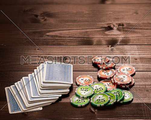 old vintage cards and a gambling chip on a wood table.