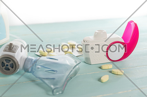 Set of asthma inhaler, anti-allergy pills and aerosol machine with inhaler mask,concept asthma and treatment on green background,copy space.