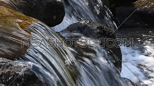 Close up brook water stream with small rift in day time, low angle side view