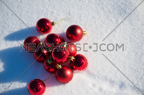 christmas red balls with long shadows  in fresh snow on beautiful sunny winter day