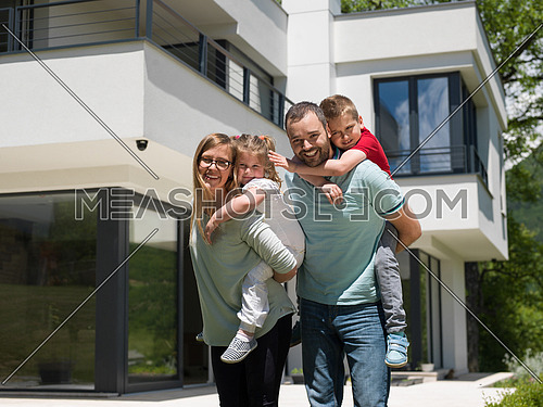 Portrait of young happy family with children in the yard in front of their luxury home of villa