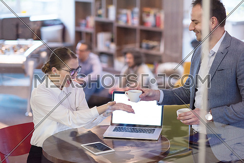 startup business people using laptop preparing for next meeting while drinking coffee and discussing ideas in creative office
