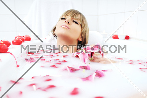 woman beauty spa and wellness treathment with red flower petals in bath with milk