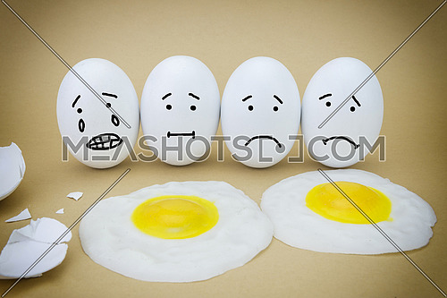Funny emotional eggs crying and laughing in the box with yolk