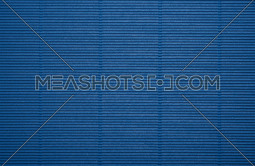 Close up background pattern texture of dark blue corrugated packaging cardboard