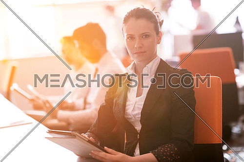 business woman working on desktop computer at modern startup office, people group in background with sunrise or sunset and sun flare in background
