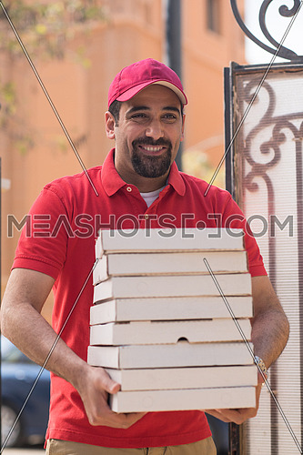 happy middle eastern pizza delivery guy with a smile delivered a delicious pizza