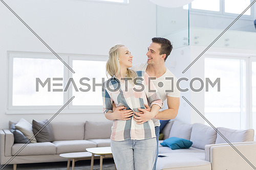 Portrait of a happy young beautiful couple hugging in their new home