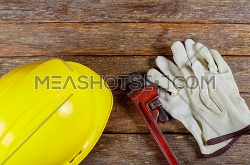 Yellow hard hat and leather work gloves and wrench construction of bunch of hand tools and helmet