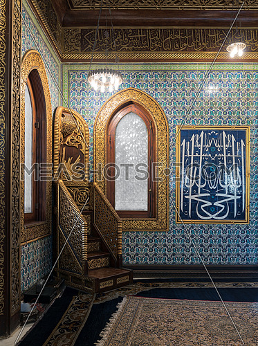 Golden ornate minbar, wooden arched window framed by golden ornate floral pattern, and floral blue pattern ceramic tiles wall at the public mosque of Manial Palace of Prince Mohammed Ali, Cairo, Egypt