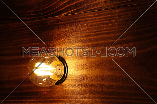 Close up one incandescent electric lamp bulb warm yellow light over wooden surface with copy space