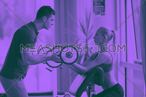 young sporty woman with trainer exercise weights lifting in fitness gym duo tone
