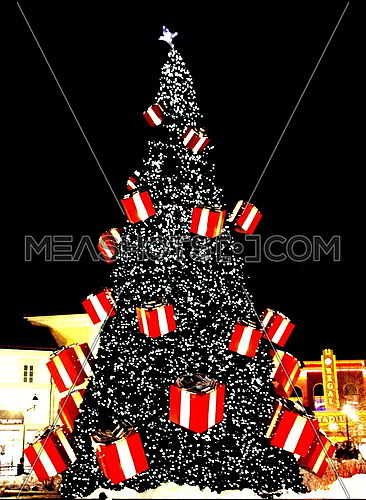 Tall Christmas tree decorated with present boxes