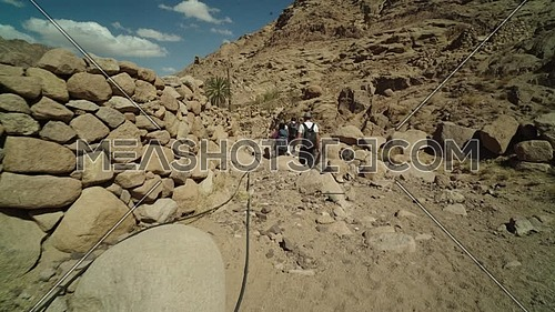 Reveal shot for group of tourists walking on big rocks besides a fence of rocks with bedouin guide to explore Sinai Mountain for wadi Freij at day.