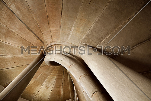 Spiral stone stair in old medieval tower, diminishing perspective, low angle view
