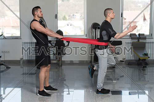 Male Couple Train Together With Resistance Bands A Leg Exercise In A Health And Fitness Concept