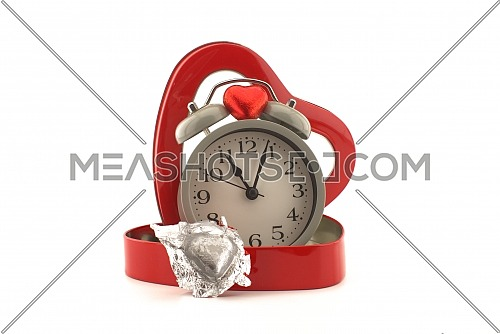 Retro alarm clock in a red heart shaped box with chocolate candy on a white background with copy space symbolic of love, togetherness and romance for Valentines