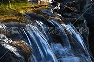 Brook water stream with small rift in day time, selective focus, angle take