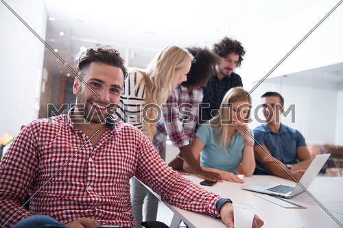 Portrait of smiling young informal businessman with colleagues in background at the office